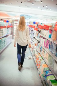 Rear view of woman carrying a shopping basket, walking among aisles with toilet paper